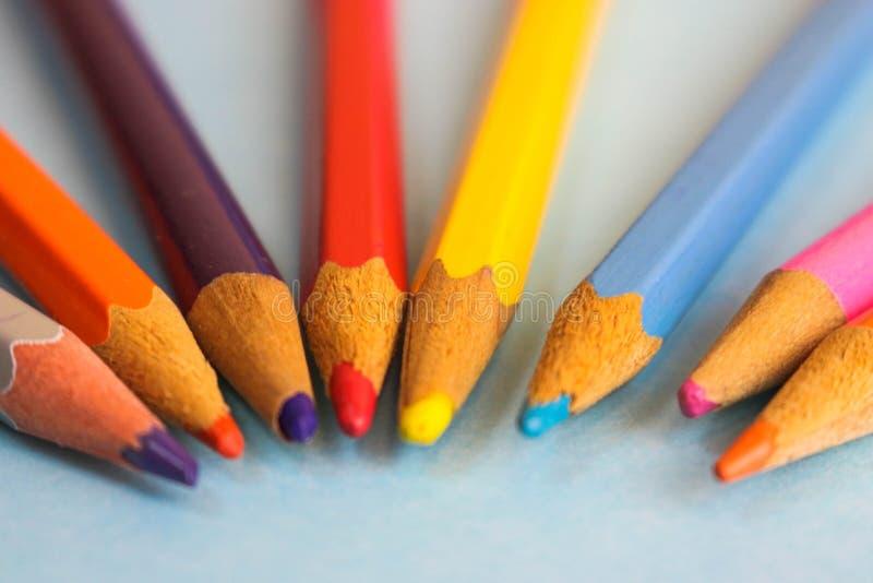 Piękni jaskrawi barwioni drewniani barwioni ostrzenie ołówki dla rysować Mieszkanie nieatutowa i odbitkowa przestrzeń na błękitny obraz stock