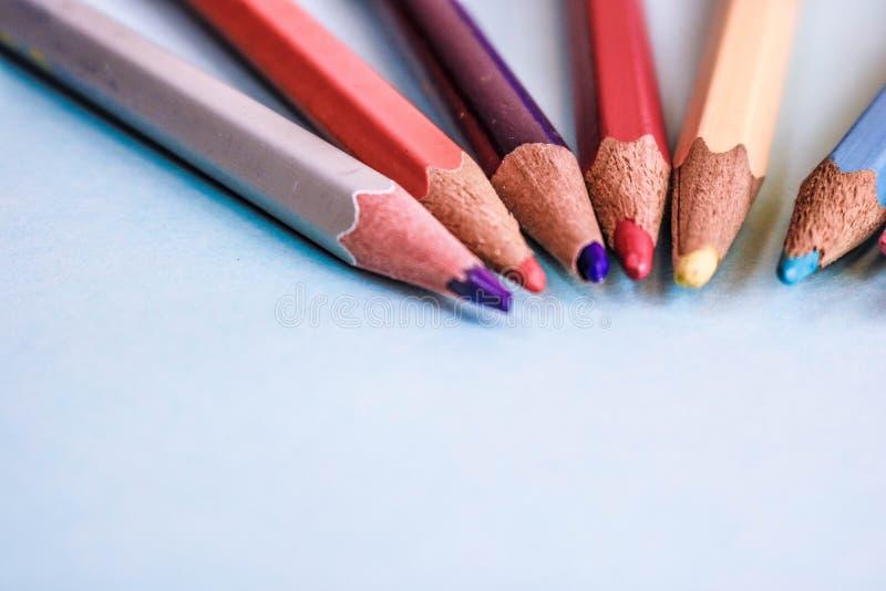 Piękni jaskrawi barwioni drewniani barwioni ostrzenie ołówki dla rysować Mieszkanie nieatutowa i odbitkowa przestrzeń na błękitny obrazy royalty free