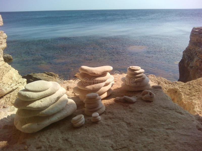 Piękni kamienie balansują na morze kamienia skały tle fotografia stock