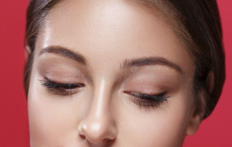 Piękni kobiet oczy i nosa zamknięty up pracowniany portret na czerwieni zdjęcie royalty free