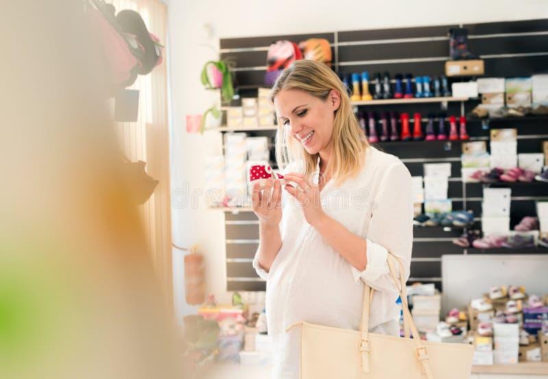 Piękni kobieta w ciąży zakupy buty dla jej dziecka fotografia stock
