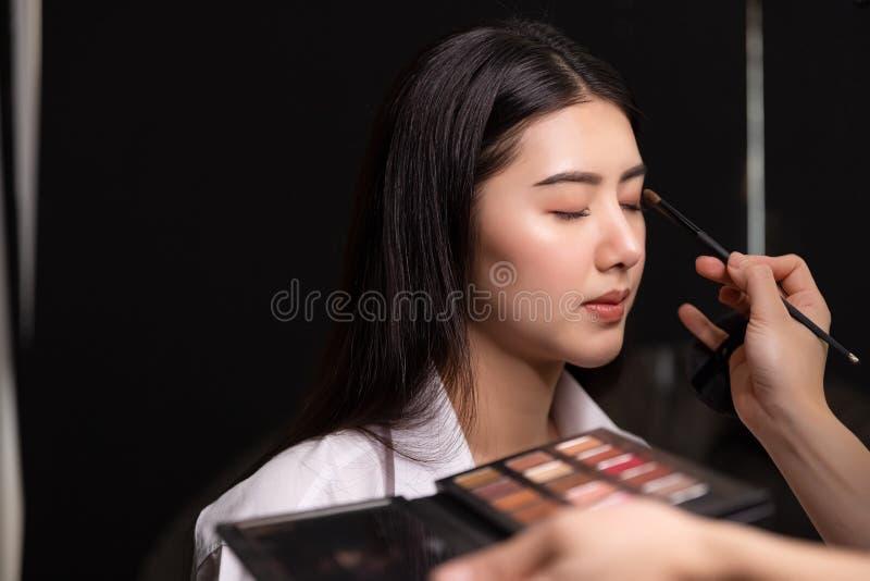 Piękni młodzi azjatykci kobiety i profesjonalisty makeup artyści stosują oko cień pi?kna twarz kobiety Perfect Makeup fotografia royalty free