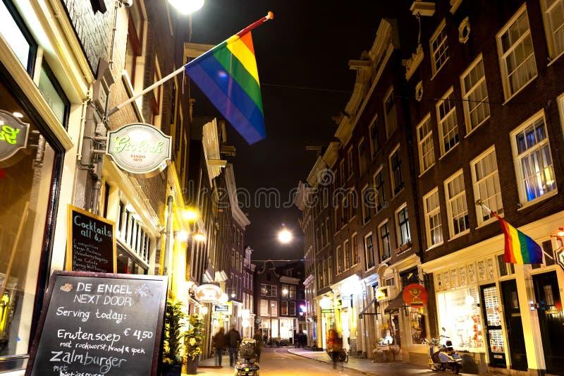 Piękni mali tradycyjni domy i bar z LGBT symbolem w Amsterdam nocą M zdjęcia stock