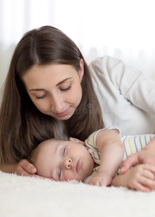 Piękni matek spojrzenia przy jej 7 miesiącami starego dziecka dosypiania w łóżku obraz royalty free