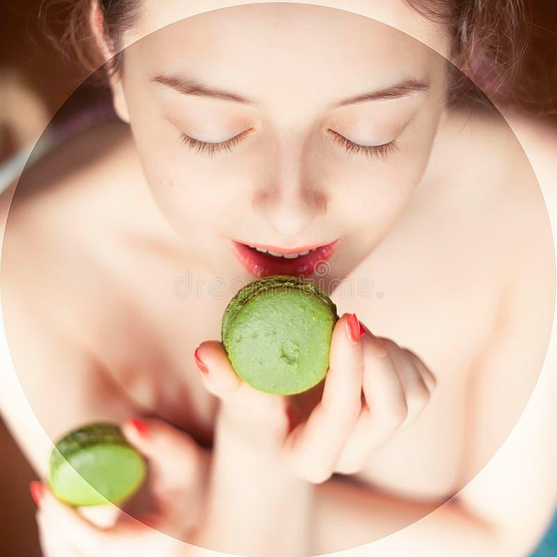 Piękni nadzy kobiety łasowania zieleni macaroons zdjęcie royalty free