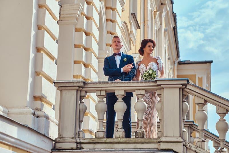 Piękni nowożeńcy ściska podczas gdy stojący na schodkach piękny stary pałac na słonecznym dniu obraz royalty free