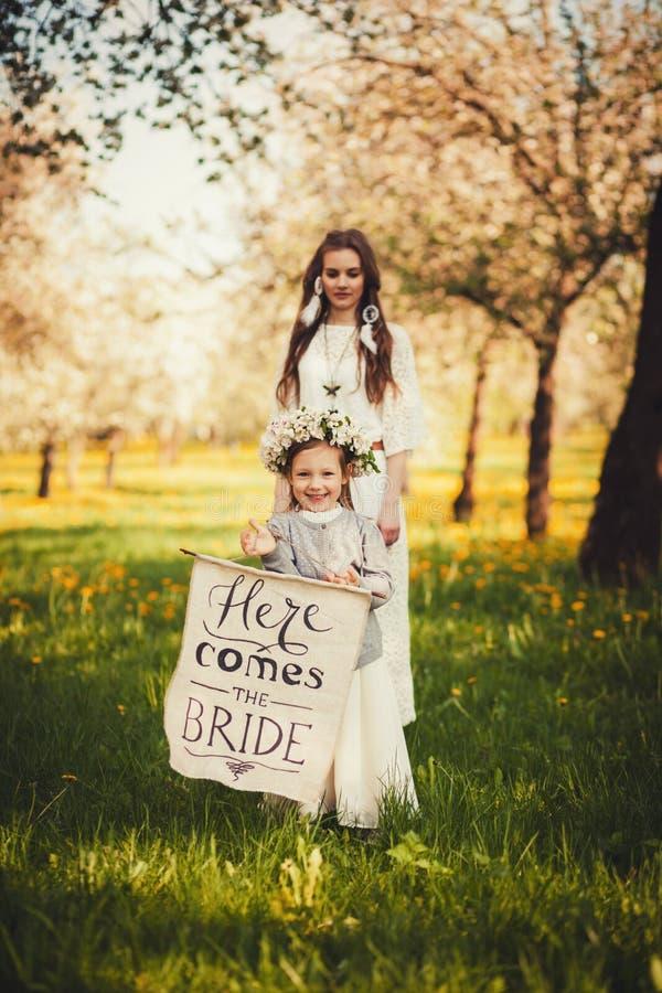 Piękni panna młoda stojaki blisko małej dziewczynki obraz stock