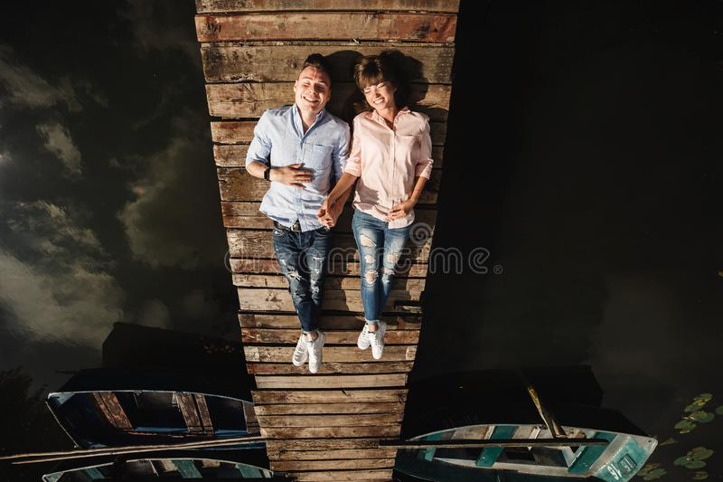 Piękni potomstwa dobierają się kłamstwa na drewnianym moście na jeziorze, spojrzenia przy each inny i uśmiechy, czule ch?opak dzi fotografia stock