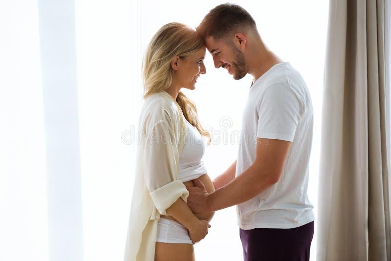 Piękni potomstwa dobierają się oczekiwać dziecka stoi wpólnie i dotyka brzucha blisko okno w domu zdjęcia royalty free