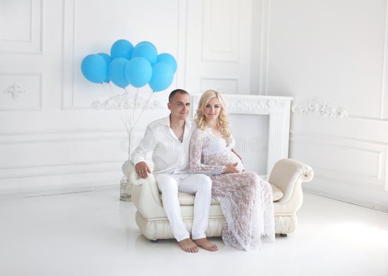 Piękni potomstwa dobierają się oczekiwać dziecka, szczęśliwa rodzina pozuje z fotografia royalty free