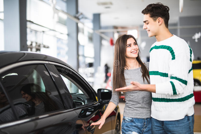 Piękni potomstwa dobierają się pozycję przy przedstawicielstwem handlowym wybiera samochód kupować Mężczyzna wskazujący na samoch obrazy stock