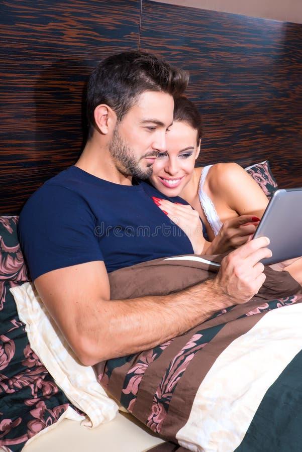 Piękni potomstwa dobierają się używać pastylka peceta w łóżku zdjęcie stock