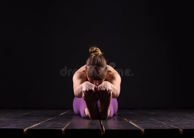 Piękni potomstwa i dysponowanego sprawność fizyczna sporta wzorcowy pozować w ciemnym studiu zdjęcie royalty free
