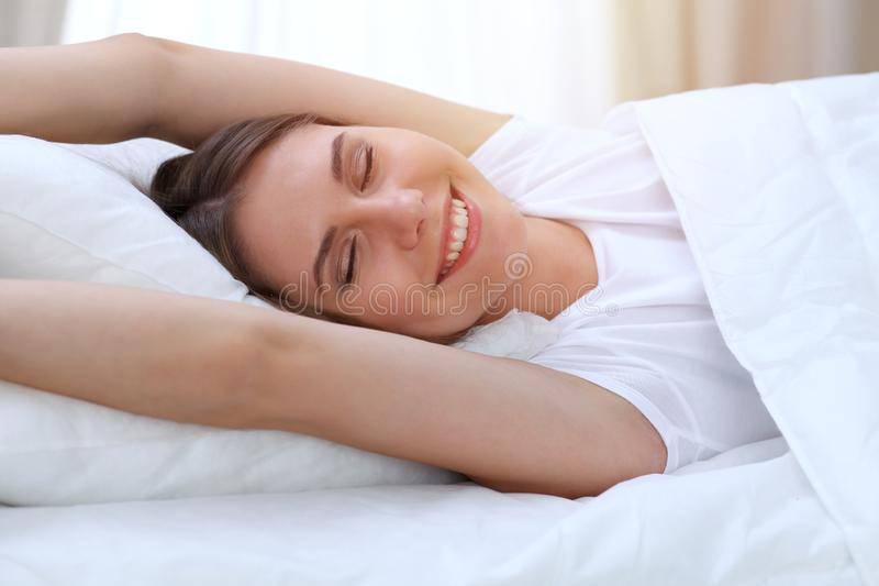 Piękni potomstwa i szczęśliwe kobiety rozciągania ręki budzą się wewnątrz podczas gdy kłamający w łóżku swobodnie i błogo ono uśm obrazy royalty free