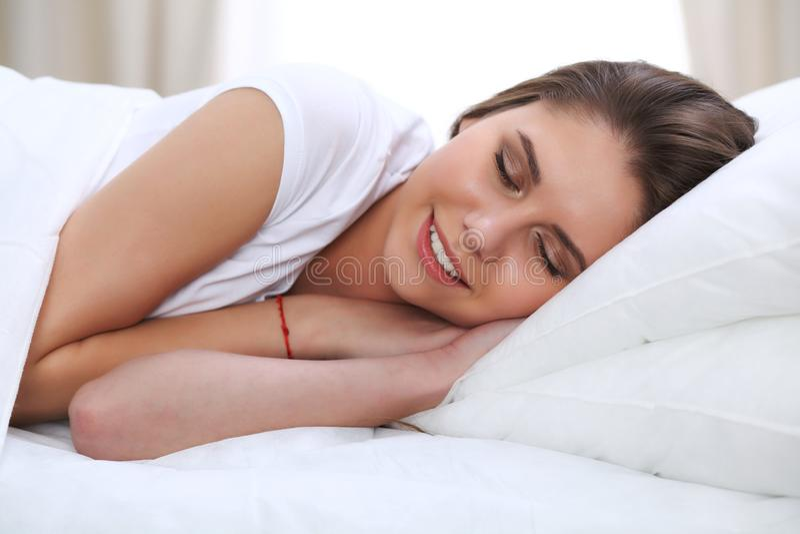 Piękni potomstwa i szczęśliwy kobiety dosypianie podczas gdy kłamający w łóżku swobodnie i blissfully ono uśmiecha się zdjęcia stock
