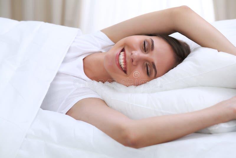 Piękni potomstwa i szczęśliwy kobiety dosypianie podczas gdy kłamający w łóżku swobodnie i blissfully ono uśmiecha się obraz royalty free