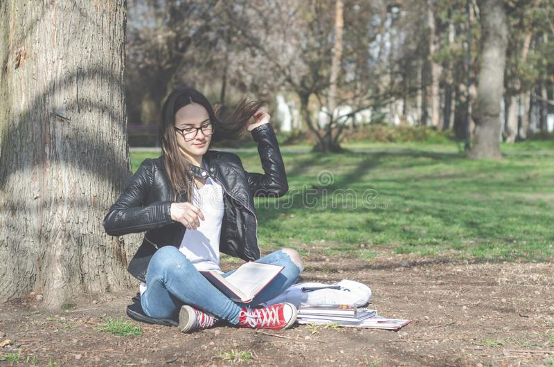 Piękni potomstwa szkoła w parkowym czytaniu, szkoły wyższa dziewczyna siedzi na ziemi z długie włosy lub eyeglasses naukę i książ obraz stock