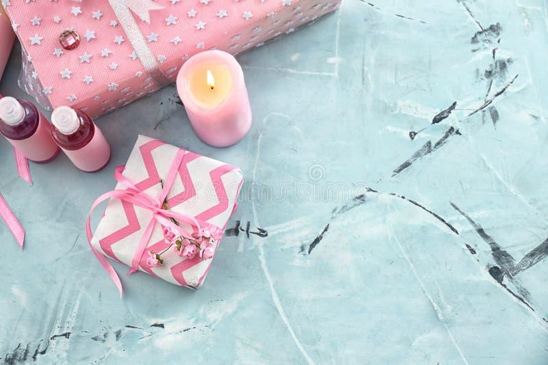 Piękni prezentów pudełka z kosmetykami i płonącą świeczką na światło stole obrazy royalty free