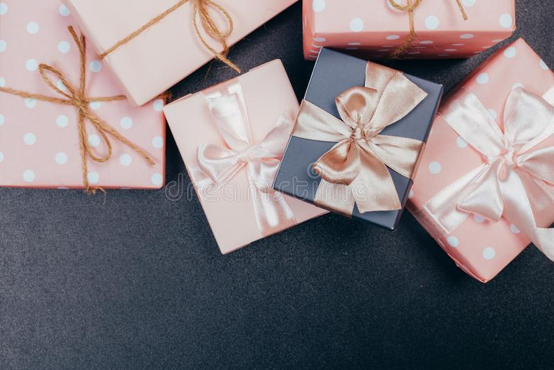 Piękni prezentów pudełka zawijający w papierze z czerwienią, złotem i menchia faborkiem na czarnej powierzchni, Odg?rny widok z k obrazy stock