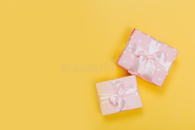 Piękni prezentów pudełka zawijający w papierze z czerwienią, złotem i menchia faborkiem na kolorze żółtym, ukazują się Odg?rny wi fotografia stock