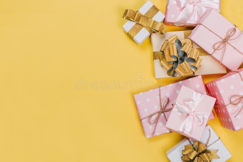 Piękni prezentów pudełka zawijający w papierze z czerwienią, złotem i menchia faborkiem na kolorze żółtym, ukazują się Odg?rny wi zdjęcia royalty free