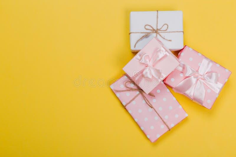 Piękni prezentów pudełka zawijający w papierze z czerwienią, złotem i menchia faborkiem na kolorze żółtym, ukazują się Odg?rny wi fotografia royalty free