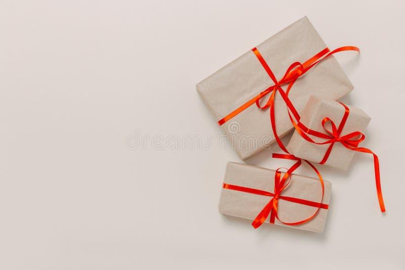Piękni prezentów pudełka zawijający w papierze z czerwonym faborkiem i łęku na beżu ukazują się Odg?rny widok z kopii przestrzeni zdjęcia stock