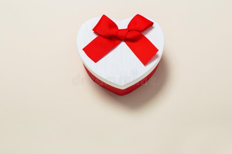 Piękni prezentów pudełka zawijający w papierze z czerwonym faborkiem i łęku na beżu ukazują się Odg?rny widok z kopii przestrzeni zdjęcie stock