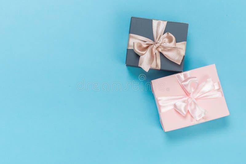 Piękni prezentów pudełka zawijający w papierze z złotem i menchia faborku na błękitnej powierzchni Odg?rny widok obrazy stock