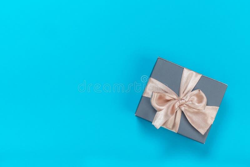 Piękni prezentów pudełka zawijający w papierze z złotem i menchia faborku na błękitnej powierzchni Odg?rny widok fotografia royalty free