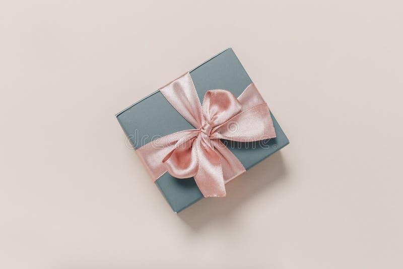 Piękni prezentów pudełka zawijający w papierze z złotem i menchia faborku na beżu ukazują się Odg?rny widok obrazy royalty free