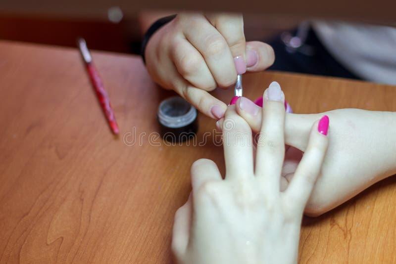Piękni robiący manikiur kobiety ` s gwoździe z różowym gwoździa połyskiem zdjęcie royalty free