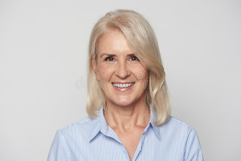 Piękni 50 rok blondynki kobiety są ono uśmiecha się odizolowywam zdjęcie royalty free