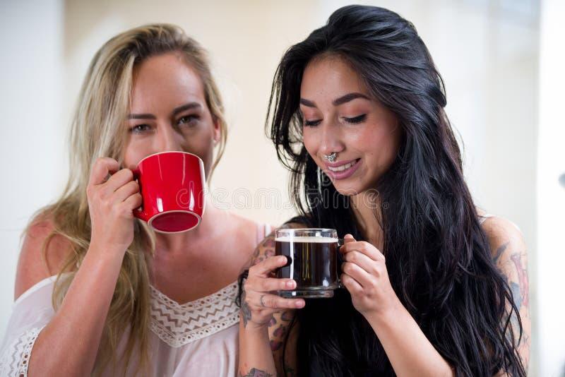 Piękni seksowni lesbians kochankowie przy ranku, blondynki i brunetki dziewczynami, piją kawę, w białym tle zdjęcia stock
