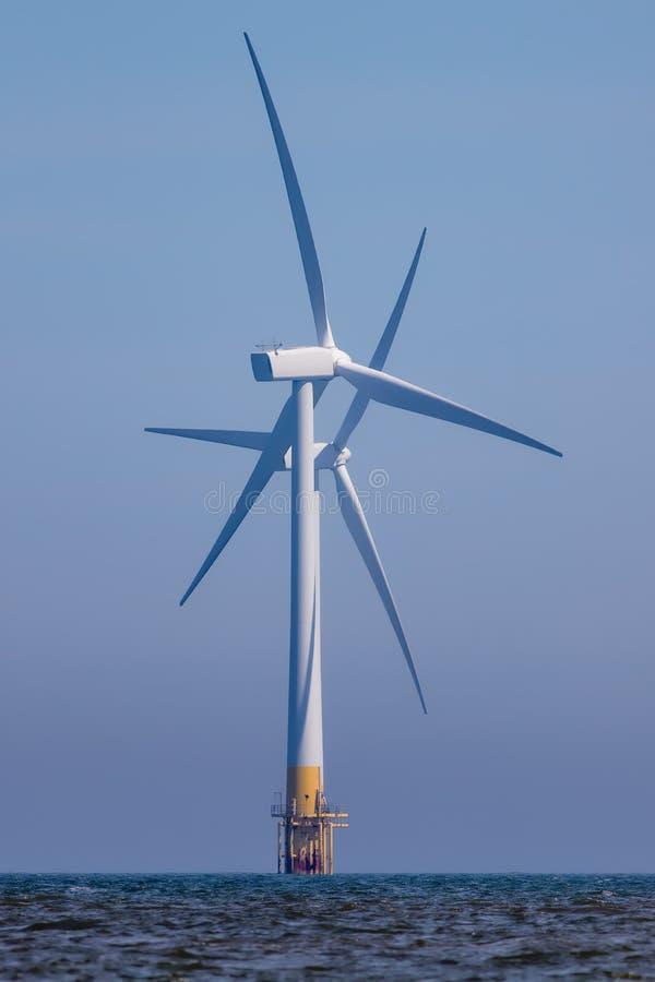 Piękni silniki wiatrowi Krzyżujący rotorowi ostrza na morzu windfarm turbina fotografia stock