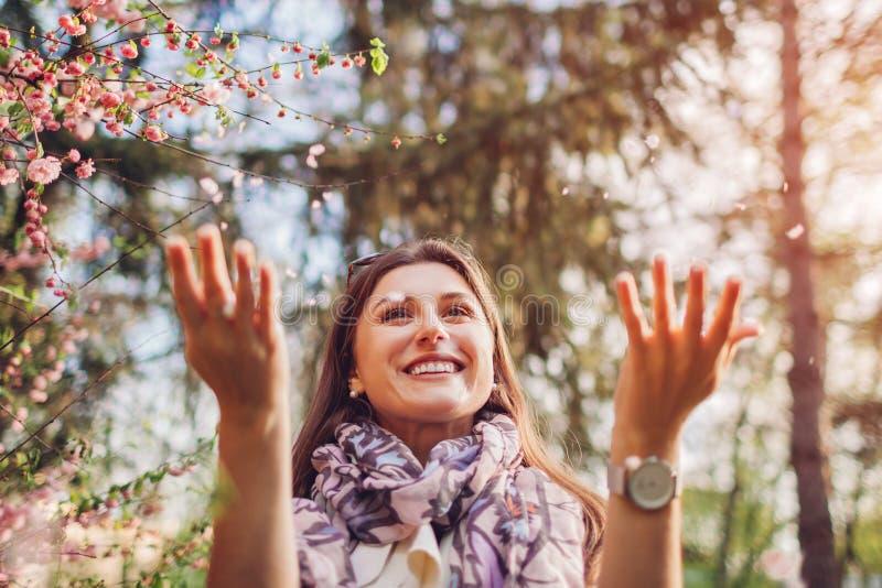 Piękni szczęśliwi kobiety miotania kwiatu płatki cieszy się kwitnącą wiosnę uprawiają ogródek dziecka ojca zabawa ma bawi? si? wp obraz stock