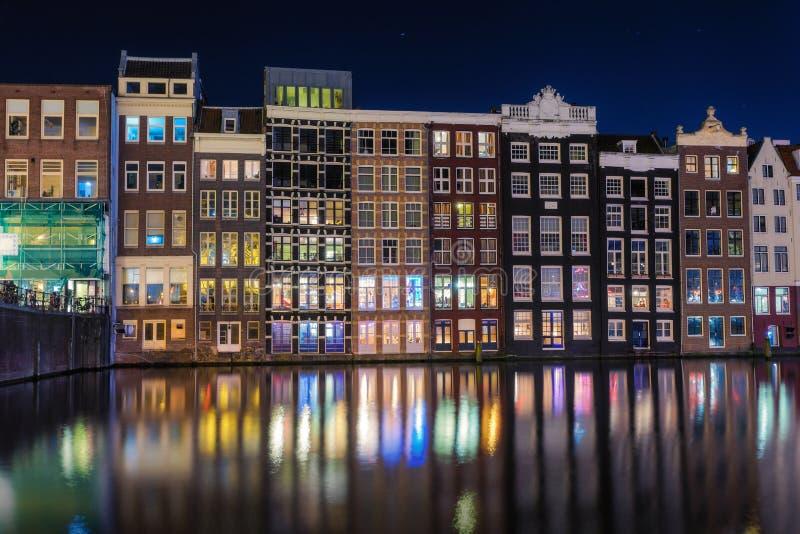 Piękni tradycyjni starzy budynki na kanale w Amsterdam przy nocą zdjęcie stock