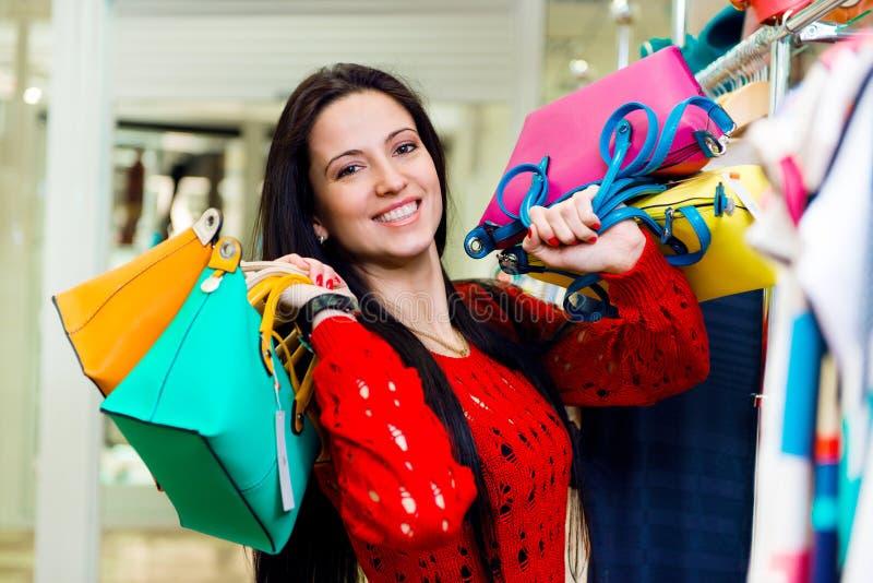Piękni uśmiechnięci młodej dziewczyny mienia torba na zakupy fotografia royalty free