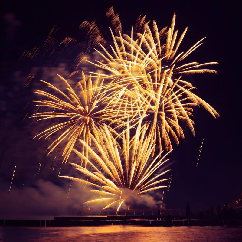 Piękni Złoci fajerwerki nad morzem na nocnego nieba tle fotografia royalty free