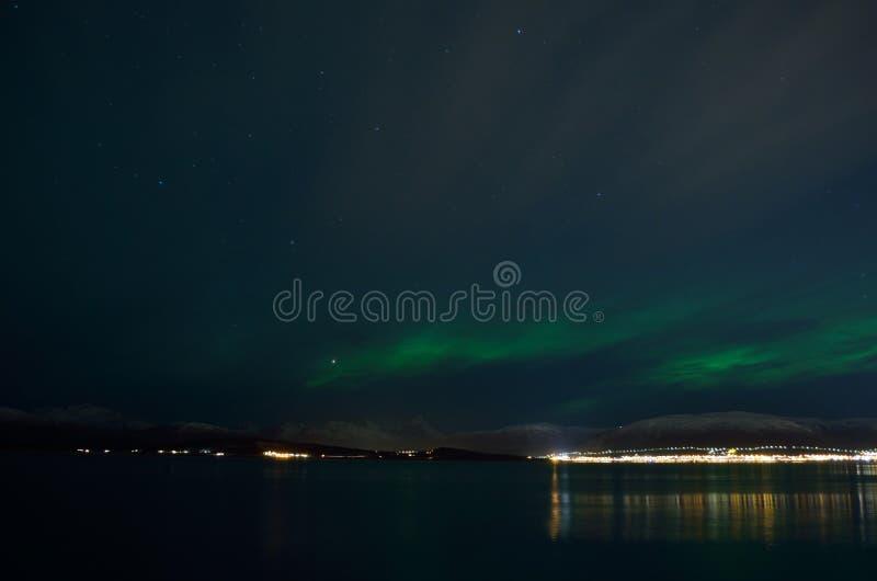 Piękni zorz borealis nad śnieżną górą i spokoju fjord z miast światłami zdjęcie royalty free