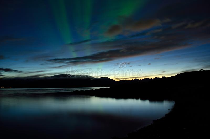 Piękni zorz borealis tanczy nad spokojnym fjord obraz royalty free