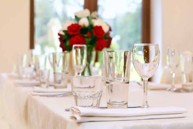 Pięknie ustawia świątecznego stół, dekorującego z bukietem róże Przygotowania dla przyjęcia obraz royalty free