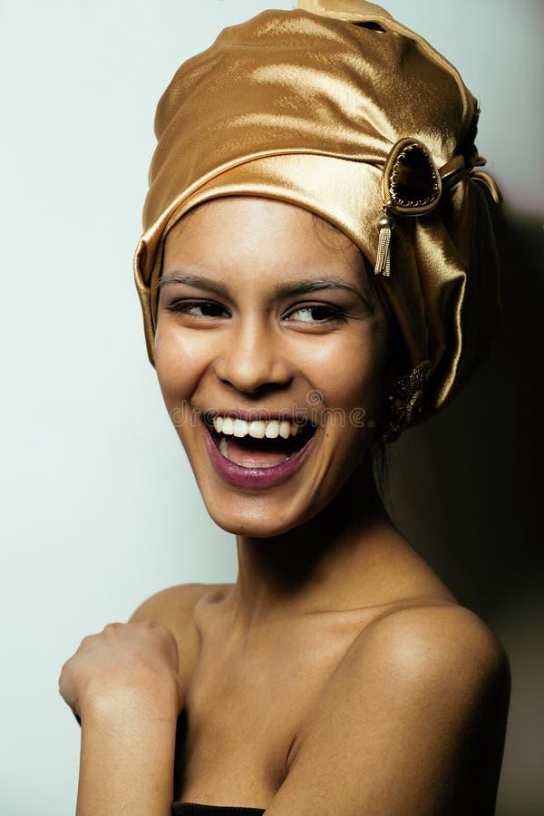 Piękno afrykańska kobieta w chuscie na głowie, bardzo elegancki spojrzenie z złocistą biżuterią fotografia royalty free