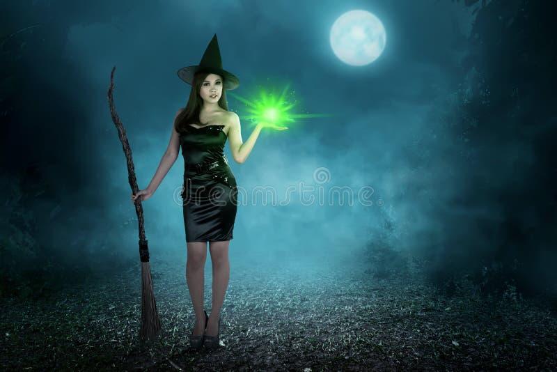 Piękno czarownicy azjatykcia kobieta z magicznym czary i latającą miotłą obrazy royalty free