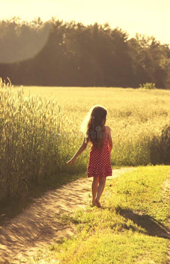 Piękno dziewczyna Outdoors cieszy się naturę Piękna mała dziewczynka w czerwieni sukni bieg na wiosny polu stonowany obraz stock