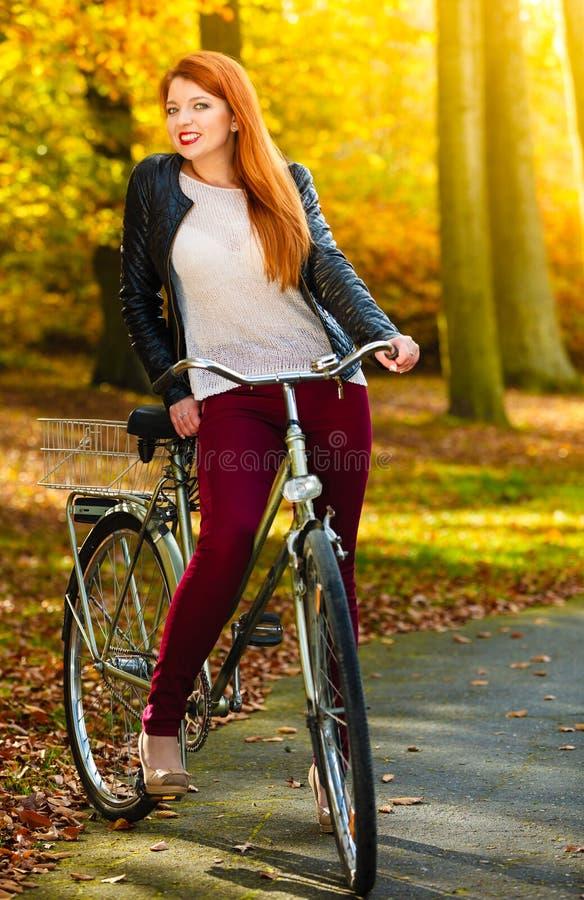 Piękno dziewczyna relaksuje w jesień parku z bicyklem, plenerowym zdjęcia royalty free