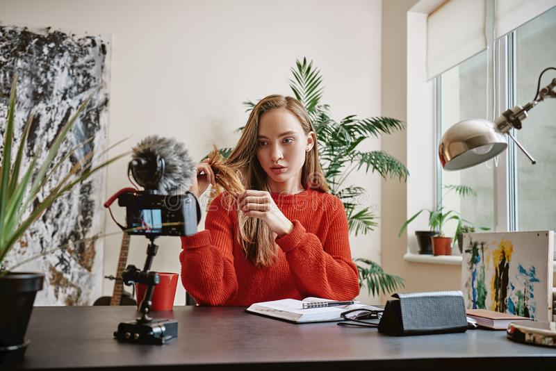 Piękno ekspert Atrakcyjny młody blogger opowiada dzienną włosianą opiekę z tripod wspinał się cyfrową kamerę obrazy royalty free