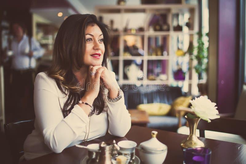 Piękno kobieta cieszy się napój po pracy Piękna uśmiechnięta w średnim wieku kobieta siedzi samotnie w kawiarni zdjęcia royalty free