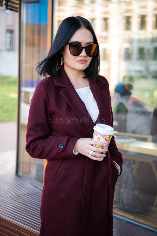 Piękno kobieta pije kawę w ulicie, plenerowy zakończenie w górę moda portreta, biurowa kobieta, zmierzchu czas, potomstwa dosyć fotografia royalty free