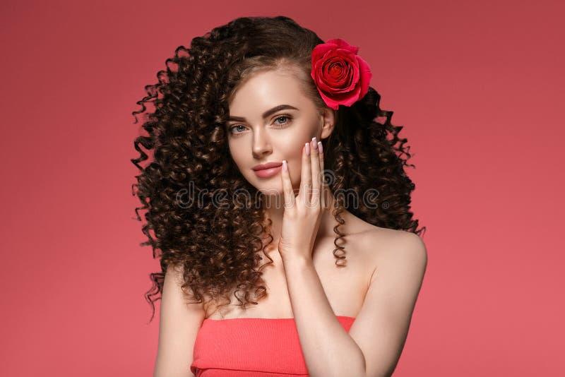 Piękno kobieta z róża kwiatu pięknym kędzierzawym włosy i wargami obraz stock